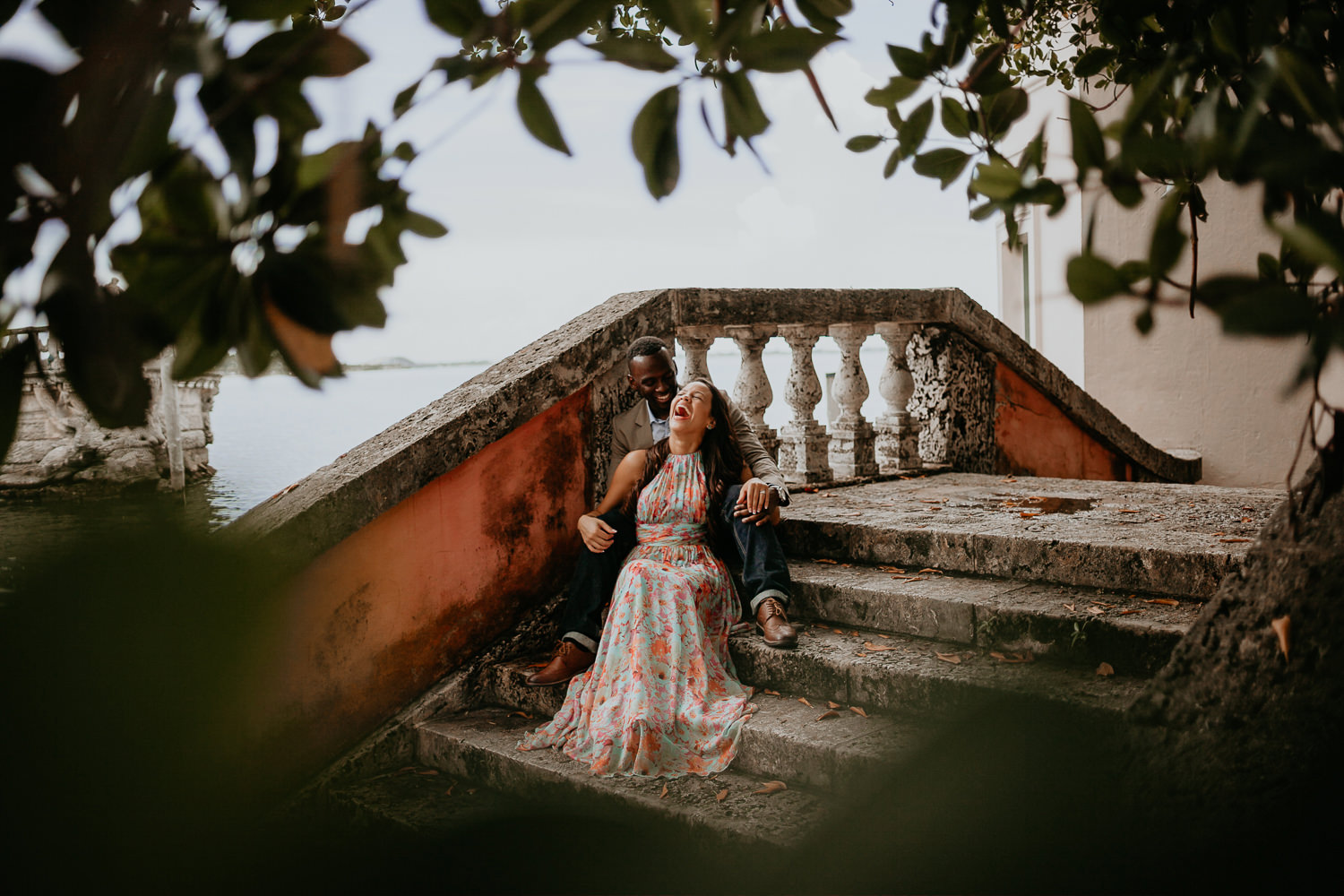 engaged couple sitting on vizcaya stone stairs