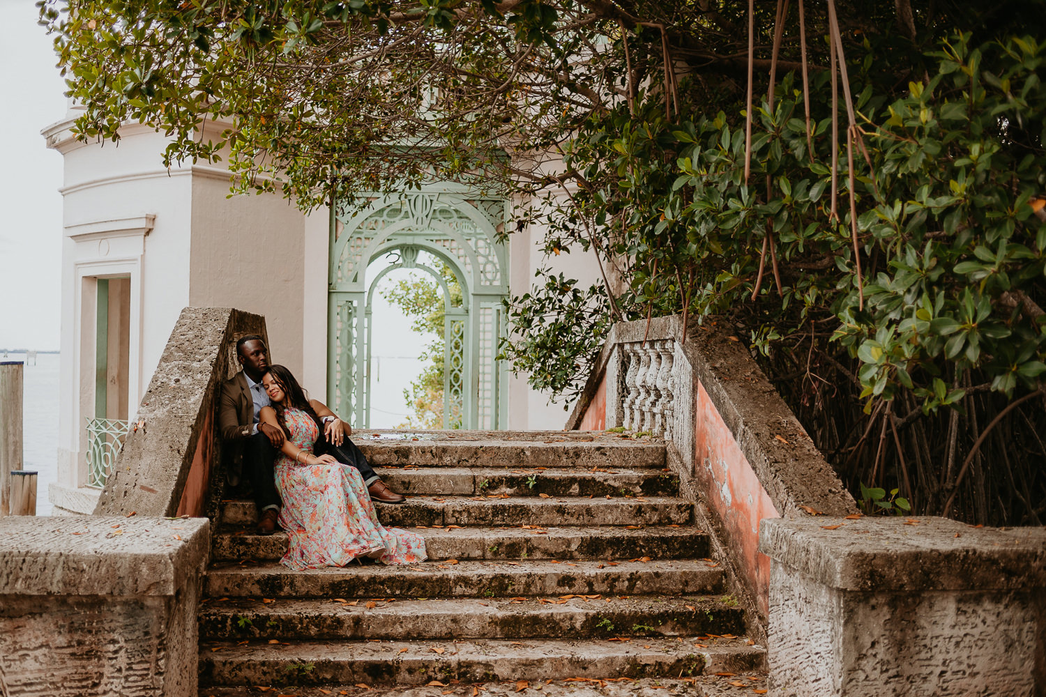 engaged couple romantically sitting on vizcaya stone stairs
