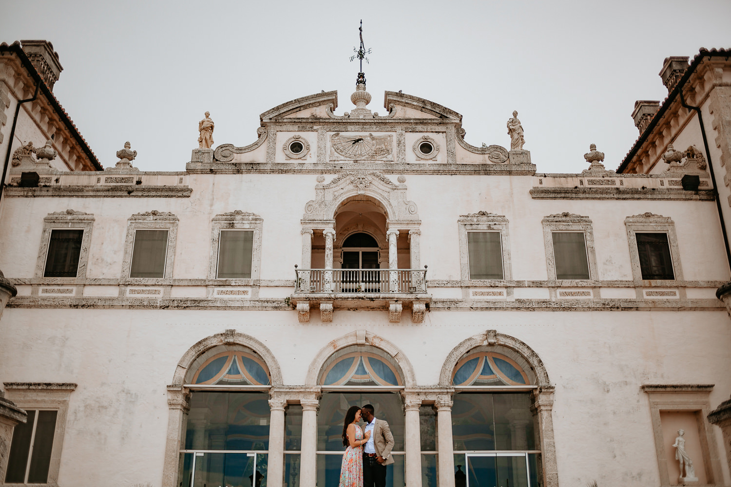 wide view of vizcaya museum house with engaged couple in the middle