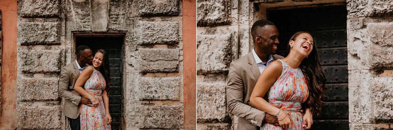 man behind fiancé kissing her cheek under stone doors