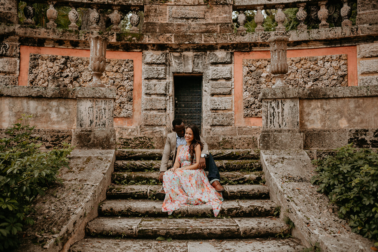 engaged couple sitting on stone steps and stone wall
