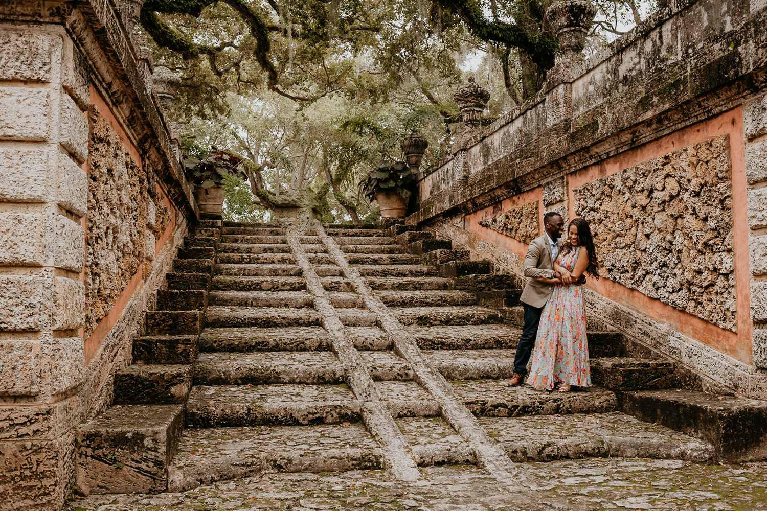 engaged couple hugging at the bottom of stone stairs at vizcaya museum