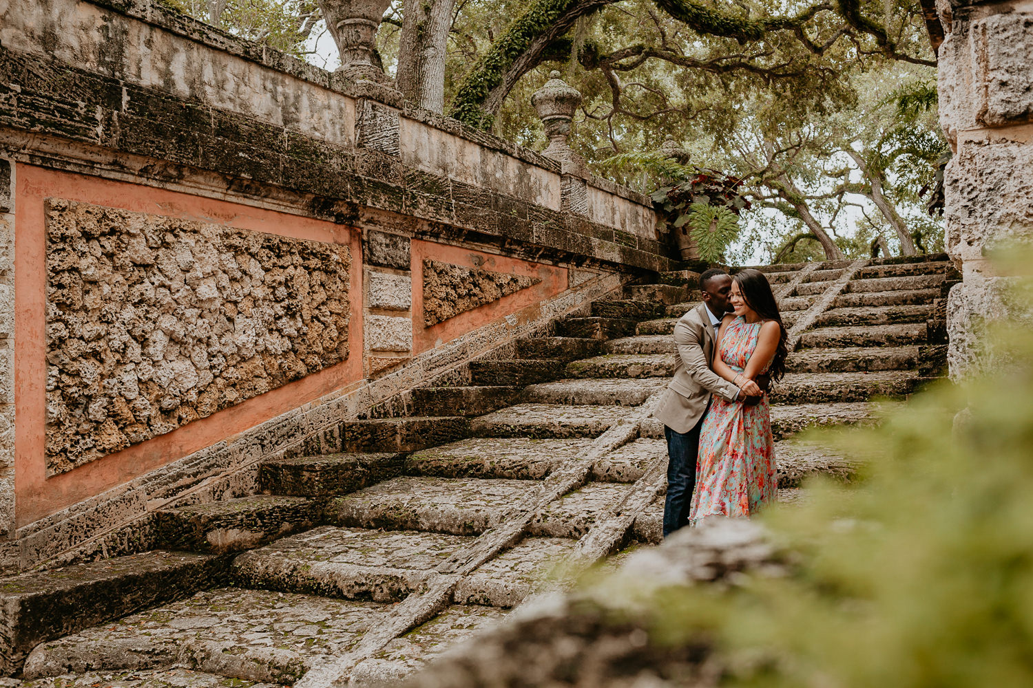 guy kissing girl on her cheek on stone stairs with oak trees in background