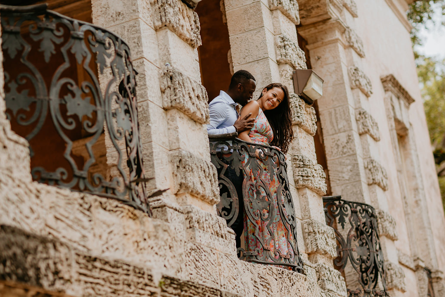 engaged couple looking over castle stone balcony guy kissing girl on shoulder