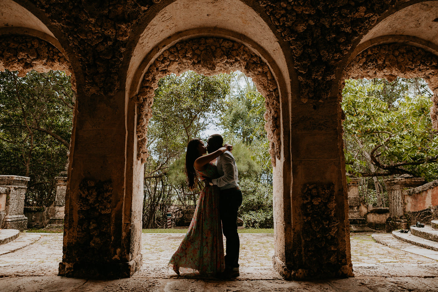 silhouette of couple in middle of castle arch and trees in background