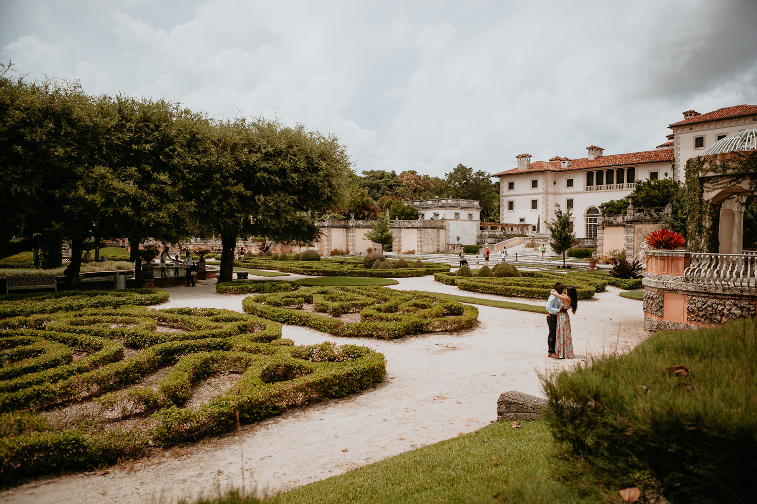 wide view of vizcaya garden with couple in the middle foreheads touching