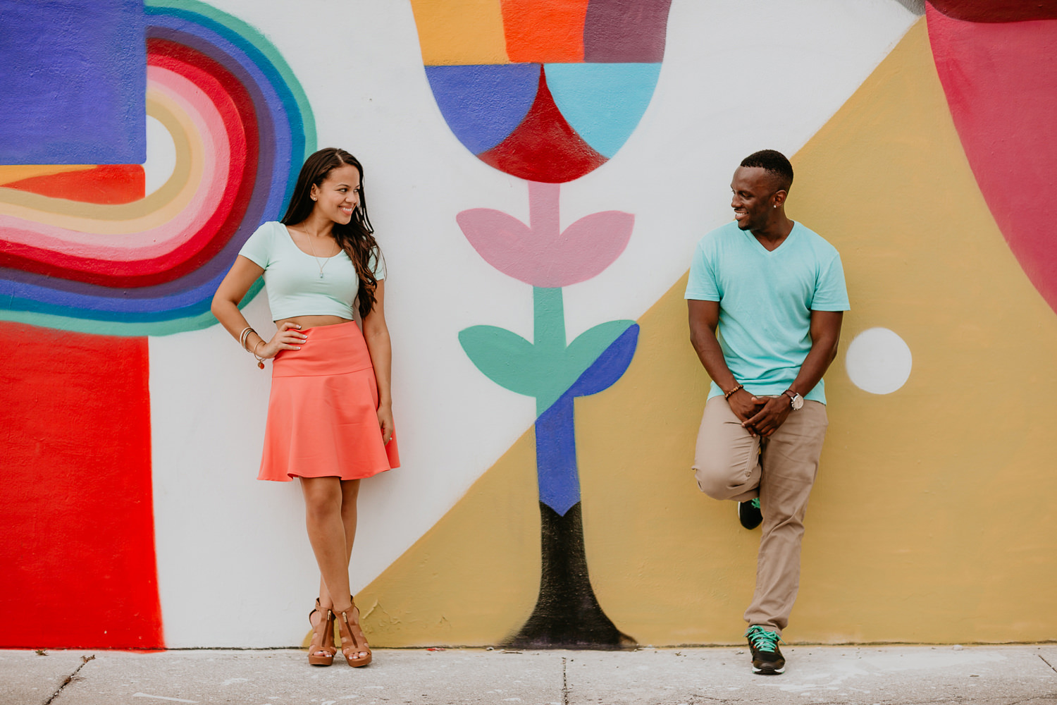 close up of couple smiling at each other leaning on colorful wall