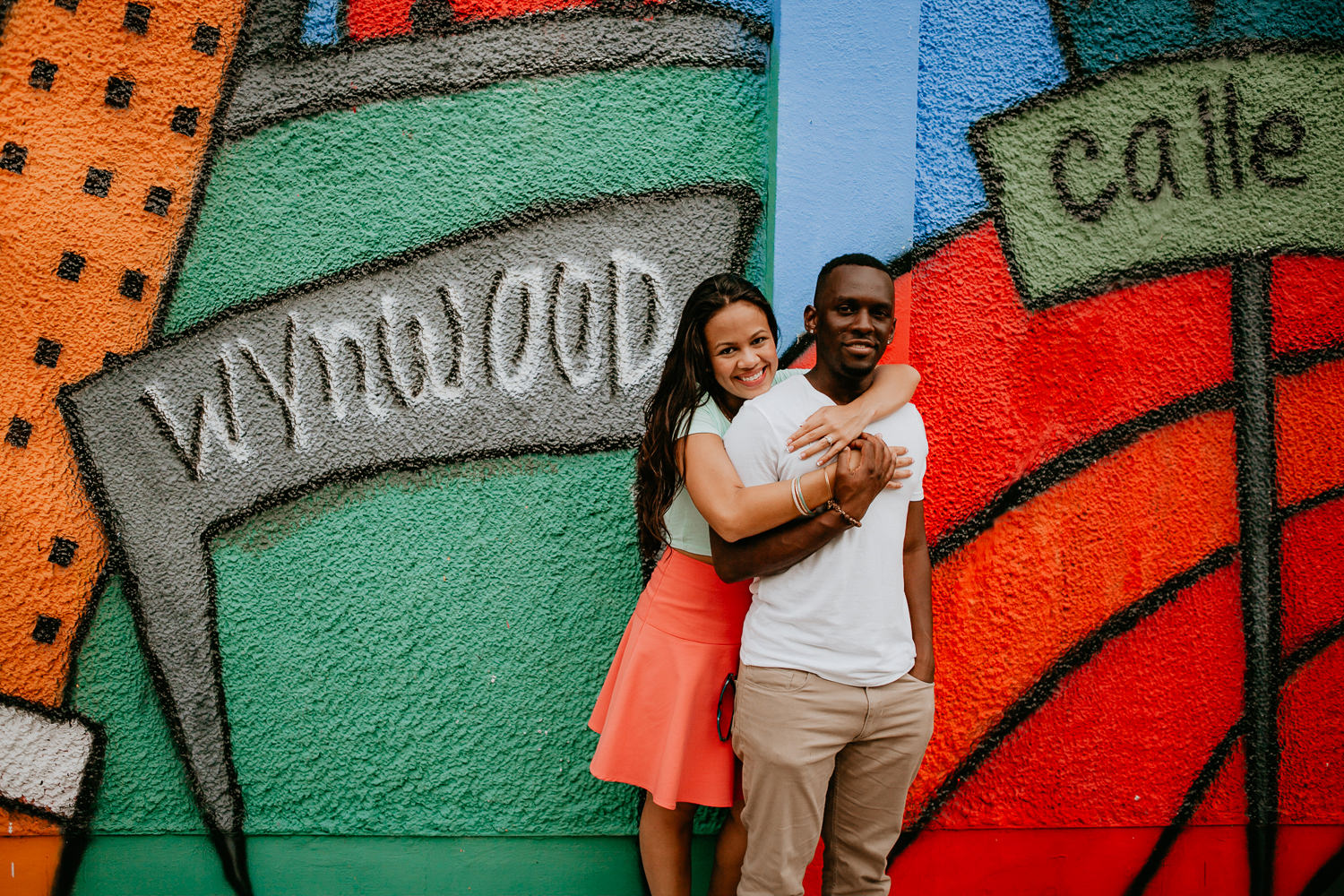 girl hugging guy from behind standing in front of Wynwood Miami wall
