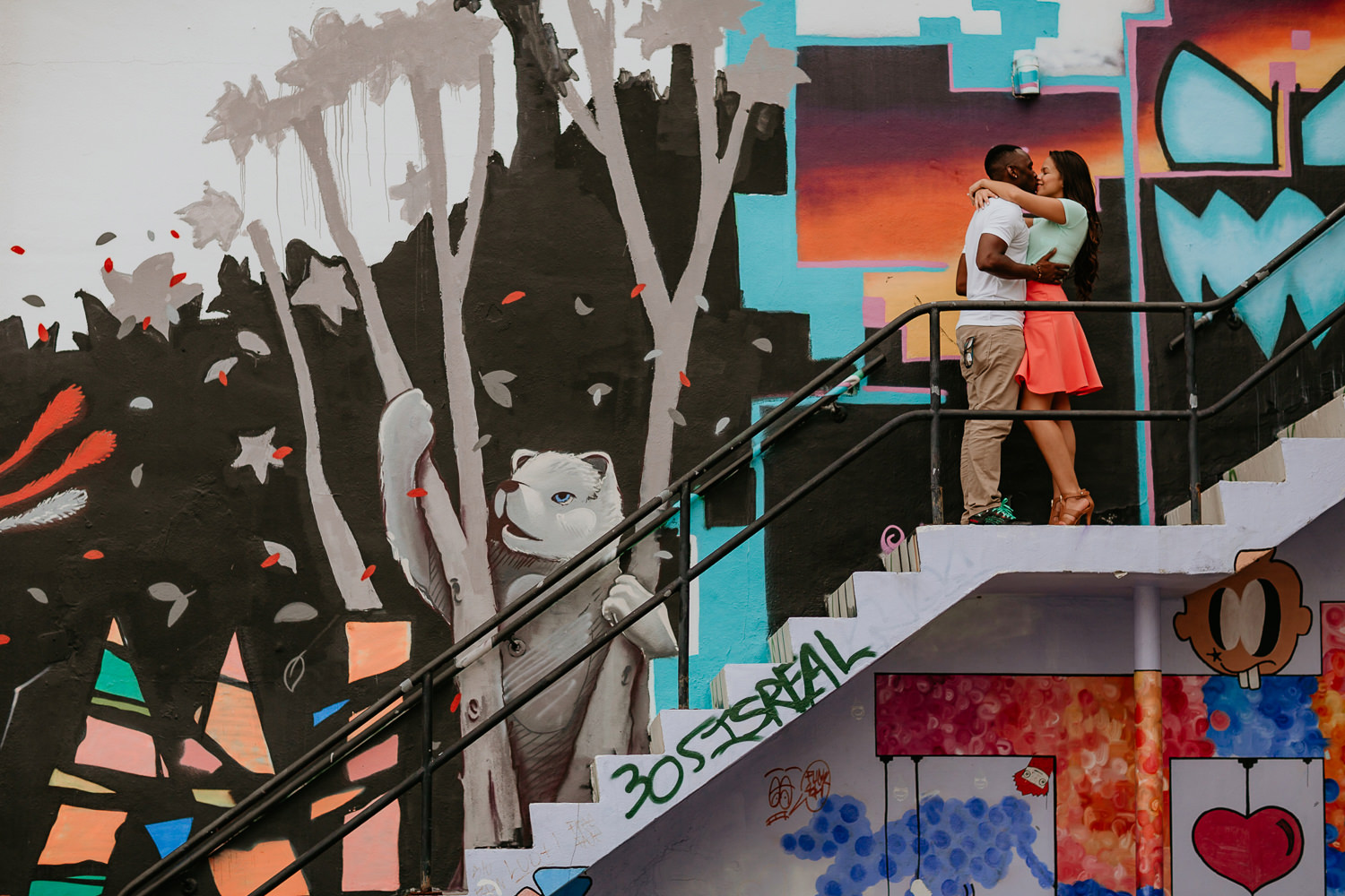 couple kissing on stairs with graffiti wall in Wynwood