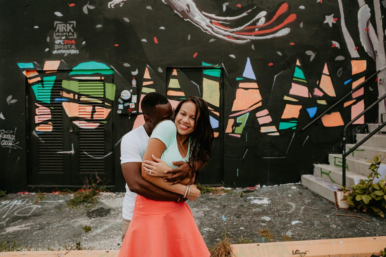 yo Miami graffiti on black wall couple hugging in middle