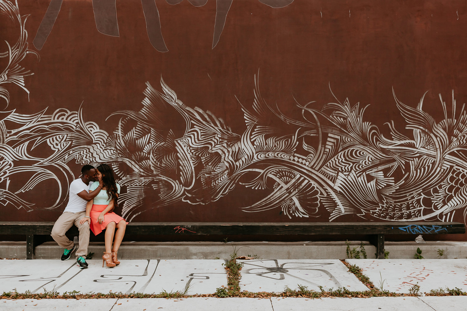 engaged couple sitting on bench with brown and white art wall
