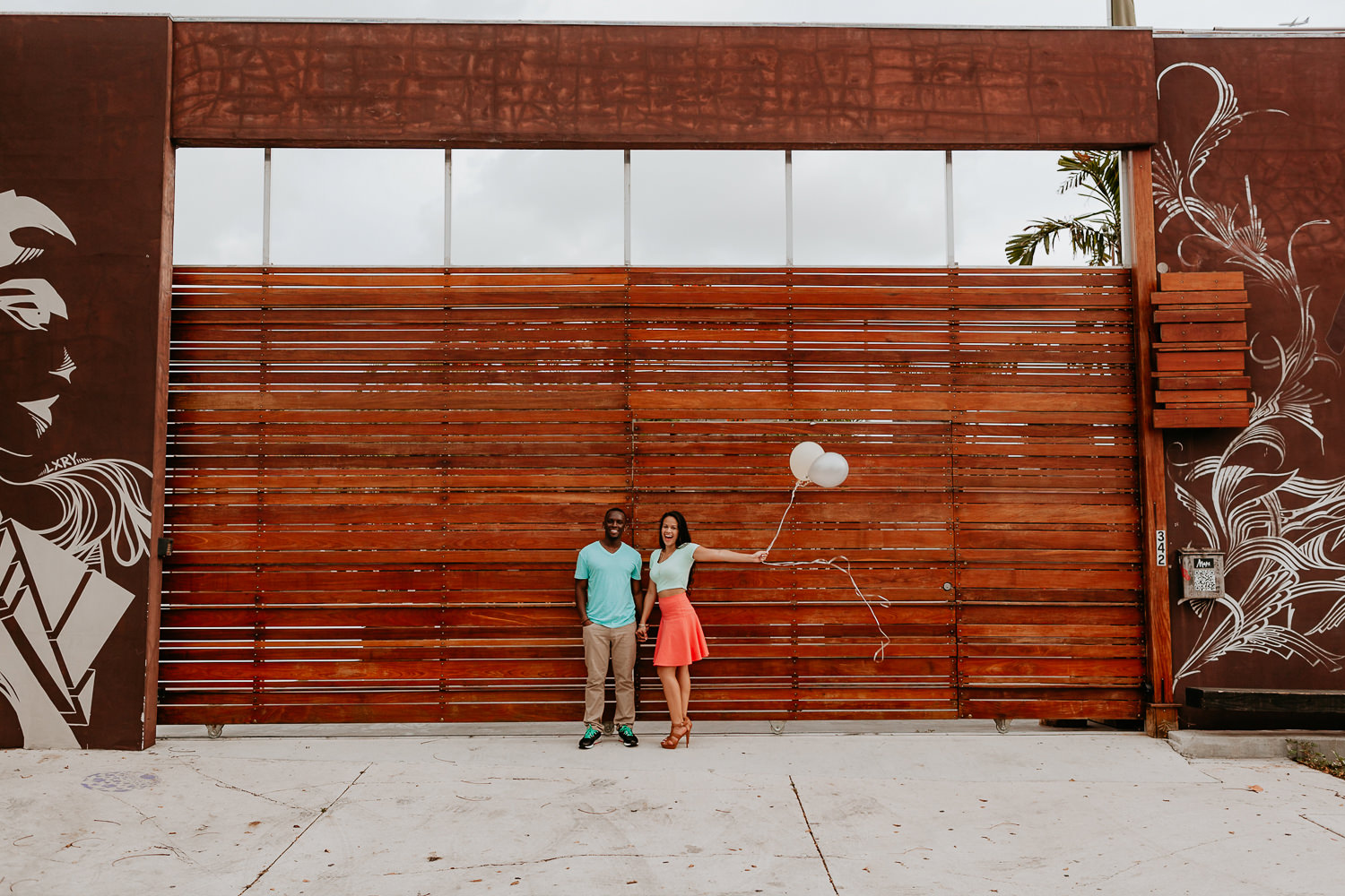 girl holding balloons holding hands with her fiancé in front of wooden gate