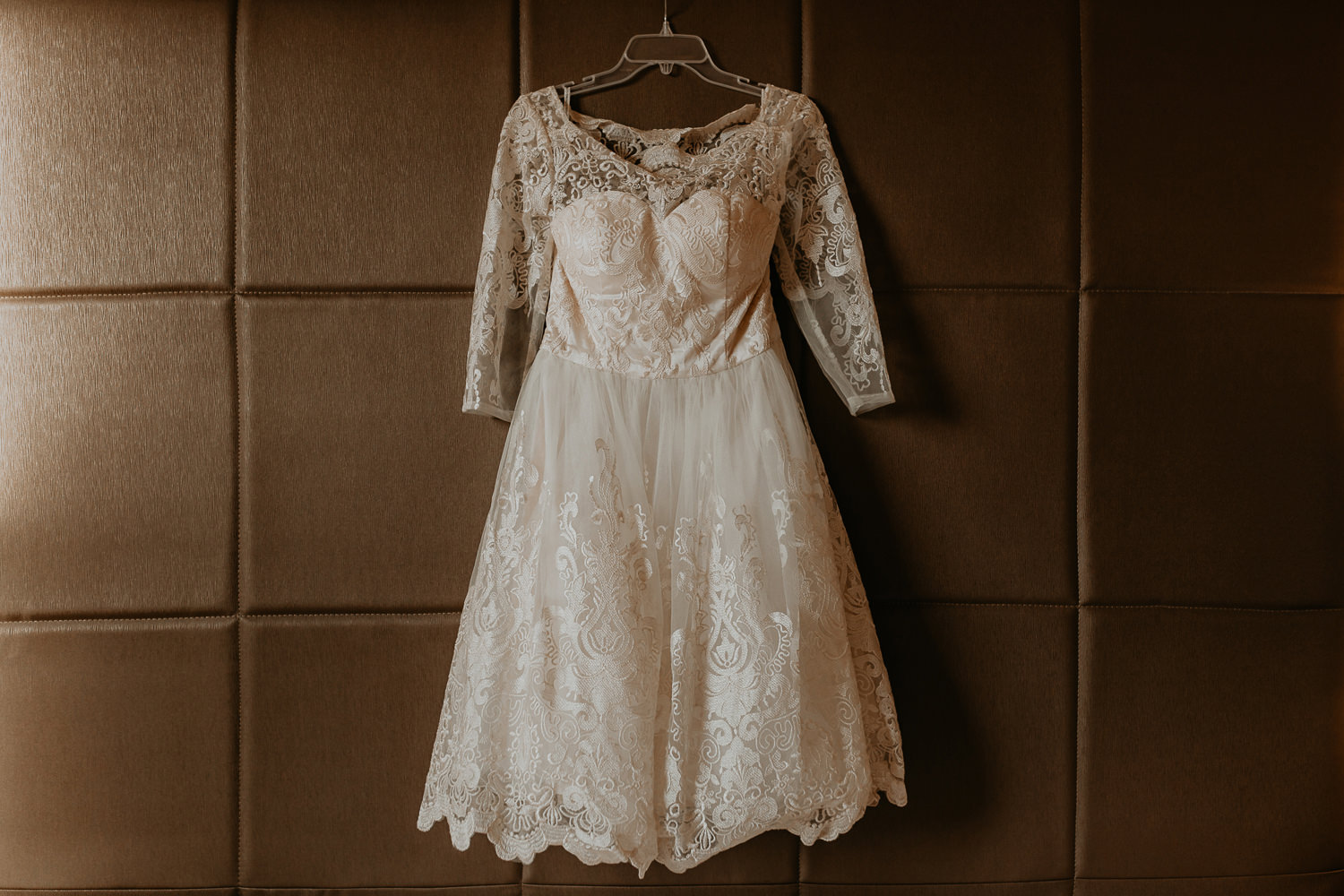 brides dress hanging on bed frame