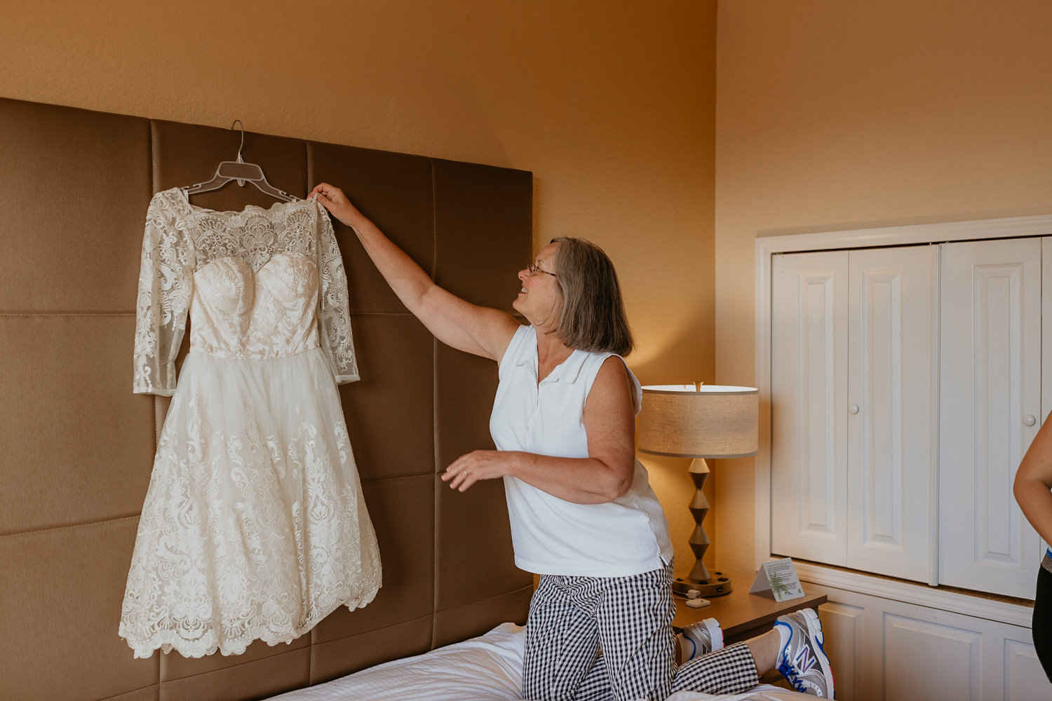 mother of the bride grabbing wedding dress from bed frame