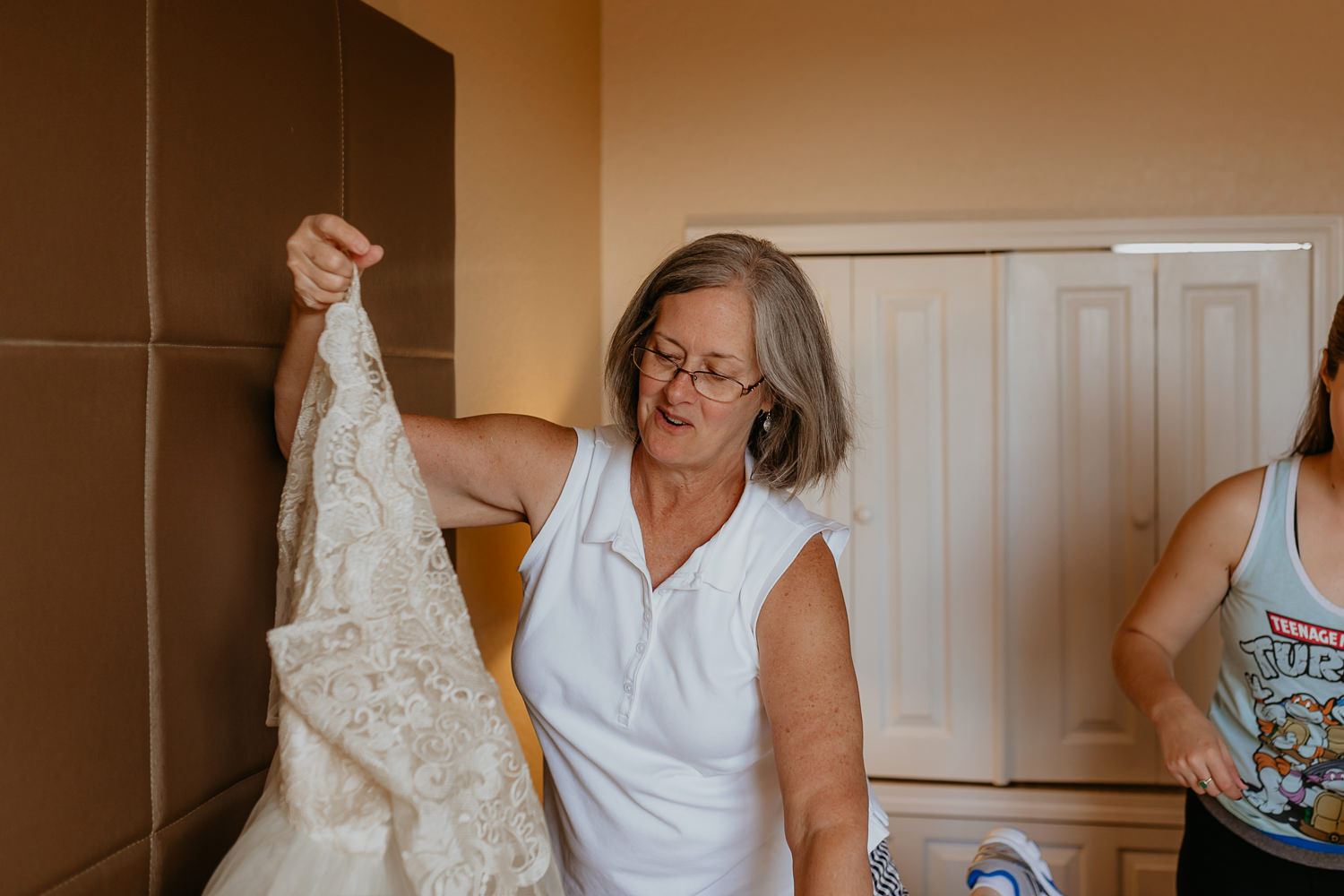 brides mom holding wedding dress