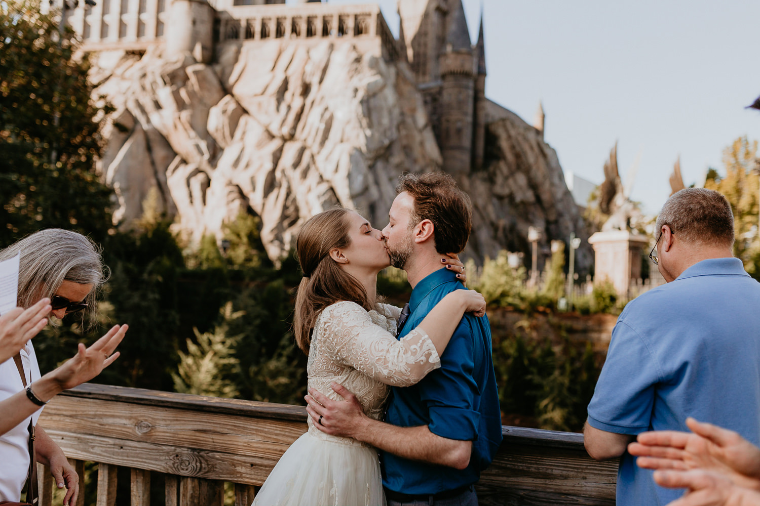 newlyweds first kiss on universal studios bridge with hogwarts castle in the background