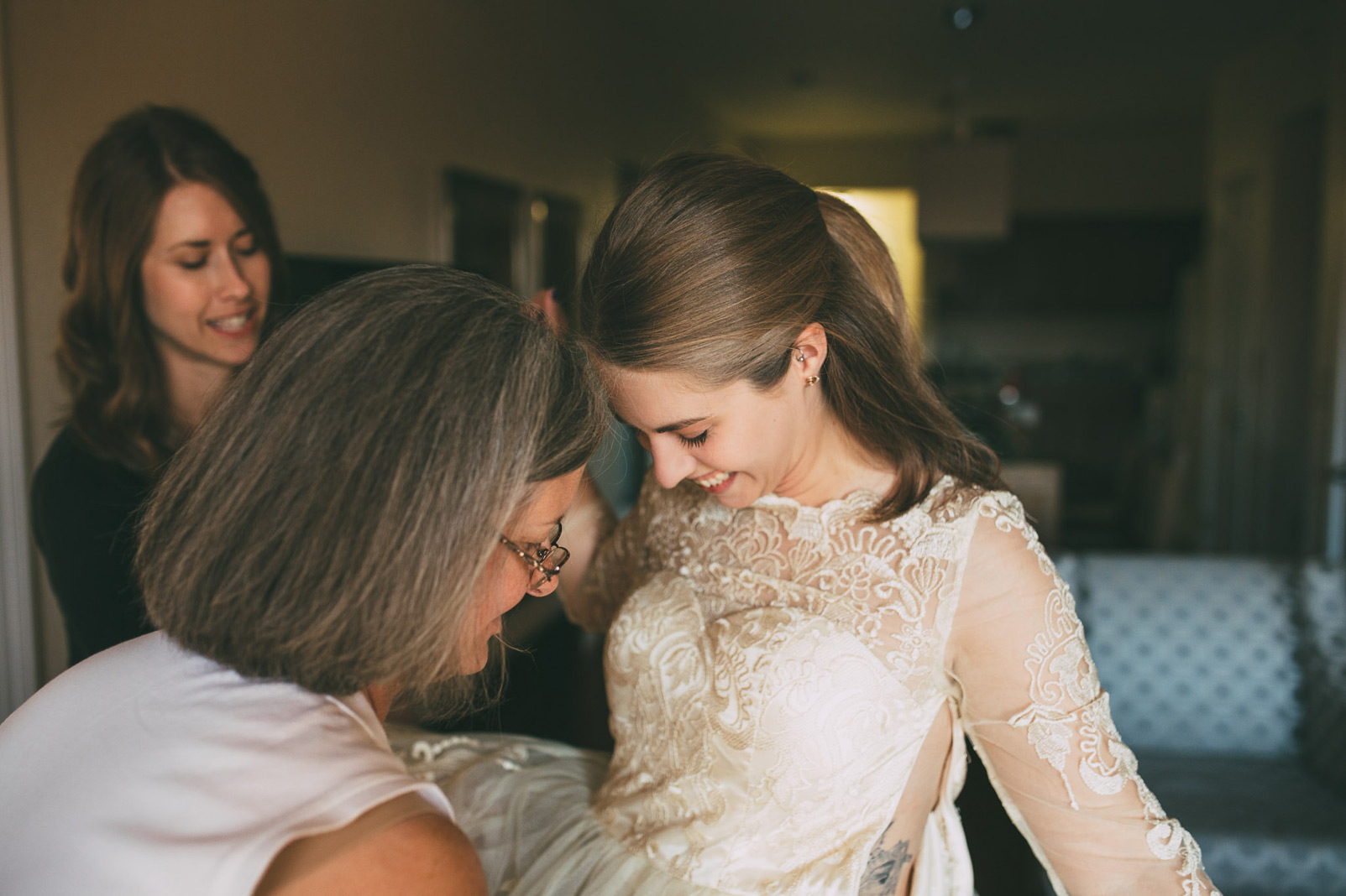 bride putting on dress laughing close up