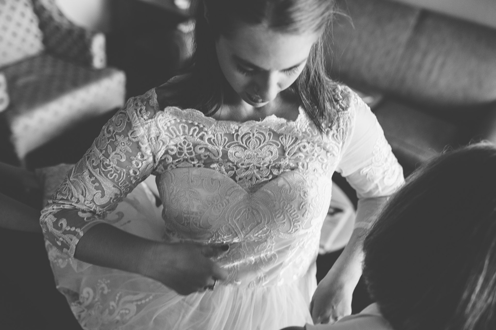 bride putting on dress close up black and white