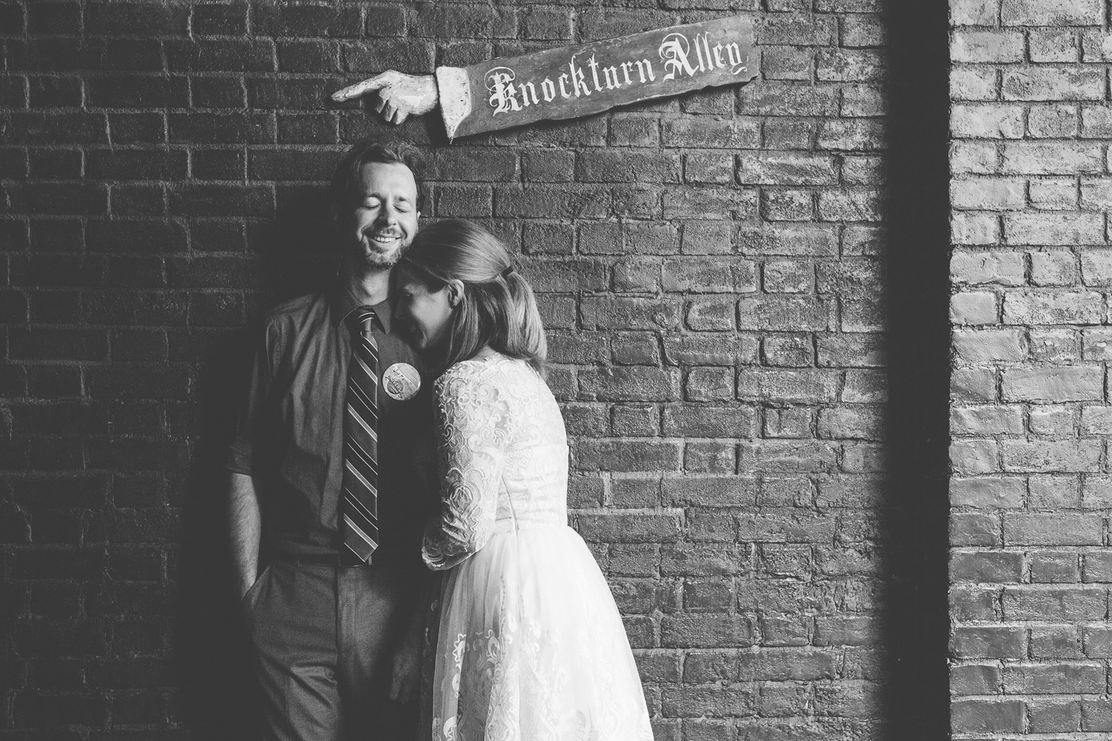 bride and groom under knockturn alley sign black and white