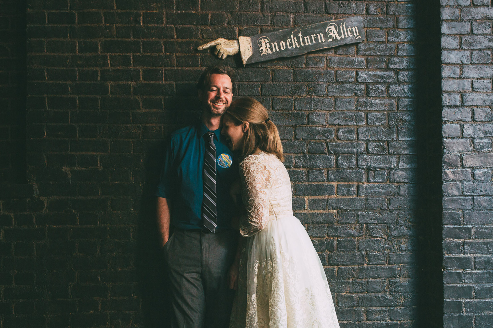 bride and groom under knockturn alley sign