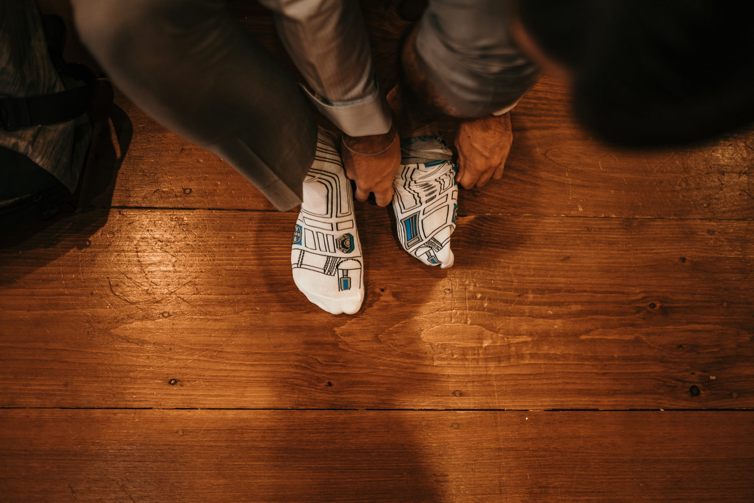 overhead picture of groom putting on R2D2 socks