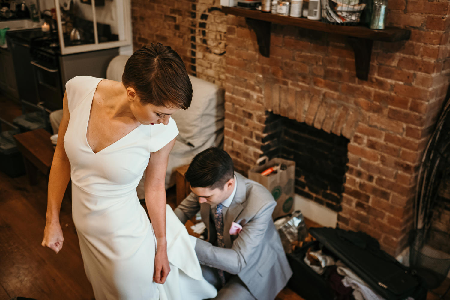 groom fixing bottom of brides dress and she's looking back at him