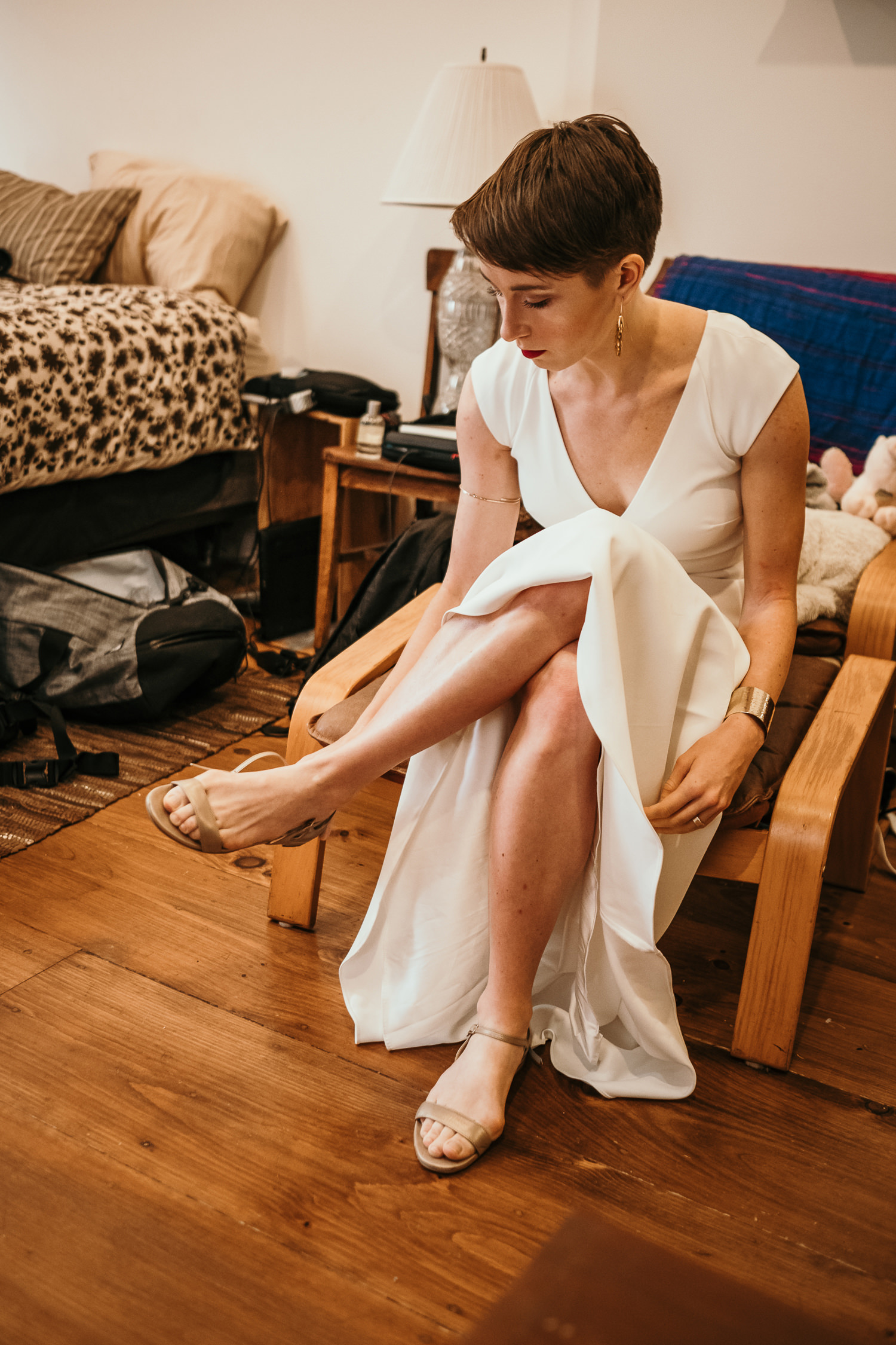 full body bride putting on her shoes sitting