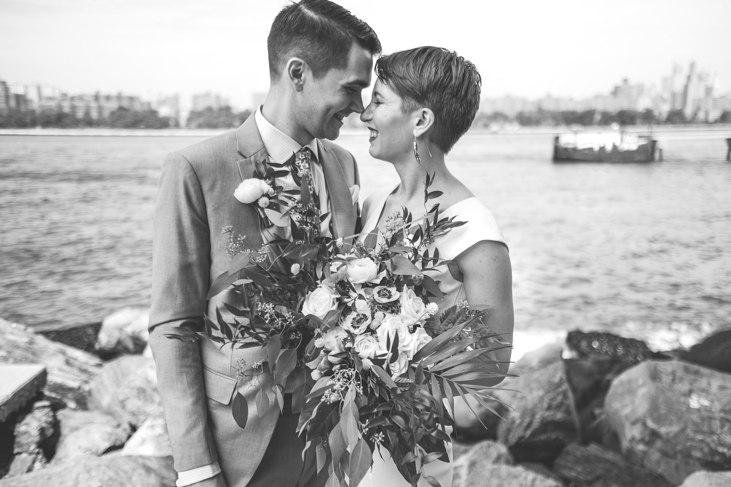 black and white close up of newlyweds noses touching holding flowers