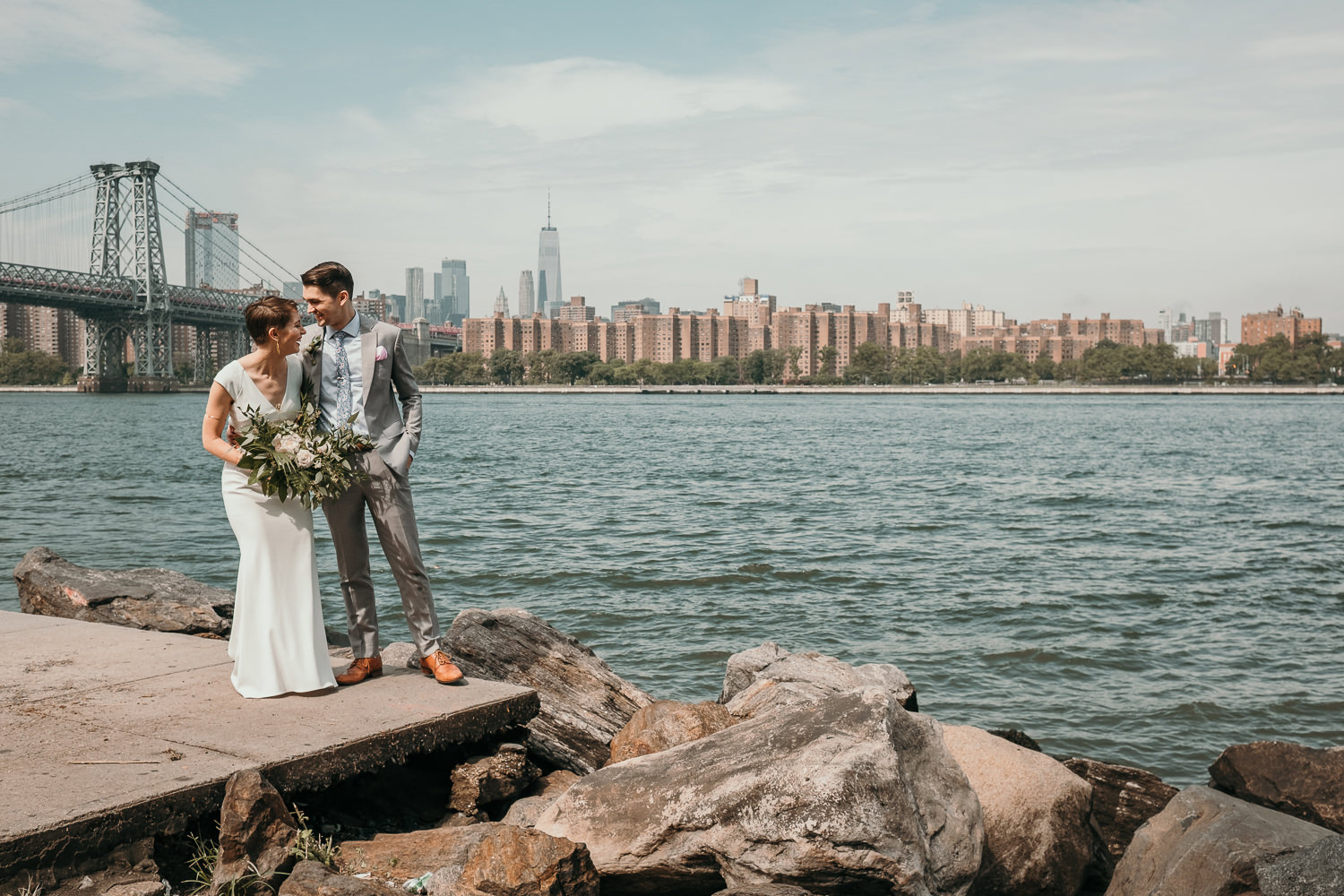 newlyweds posing near water Williamsburg bride and NYC skyline in background