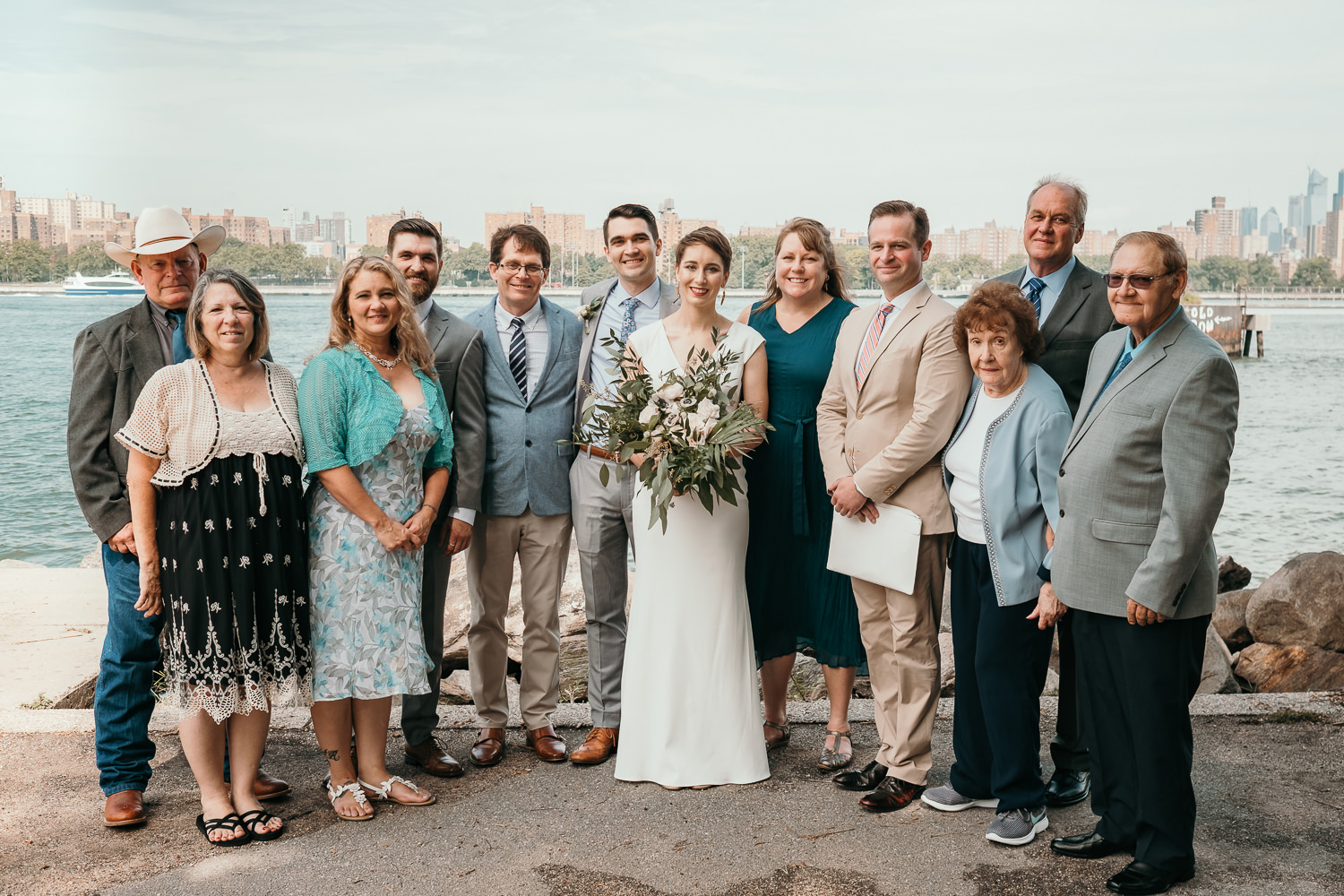 immediate family picture near water newlyweds in the middle