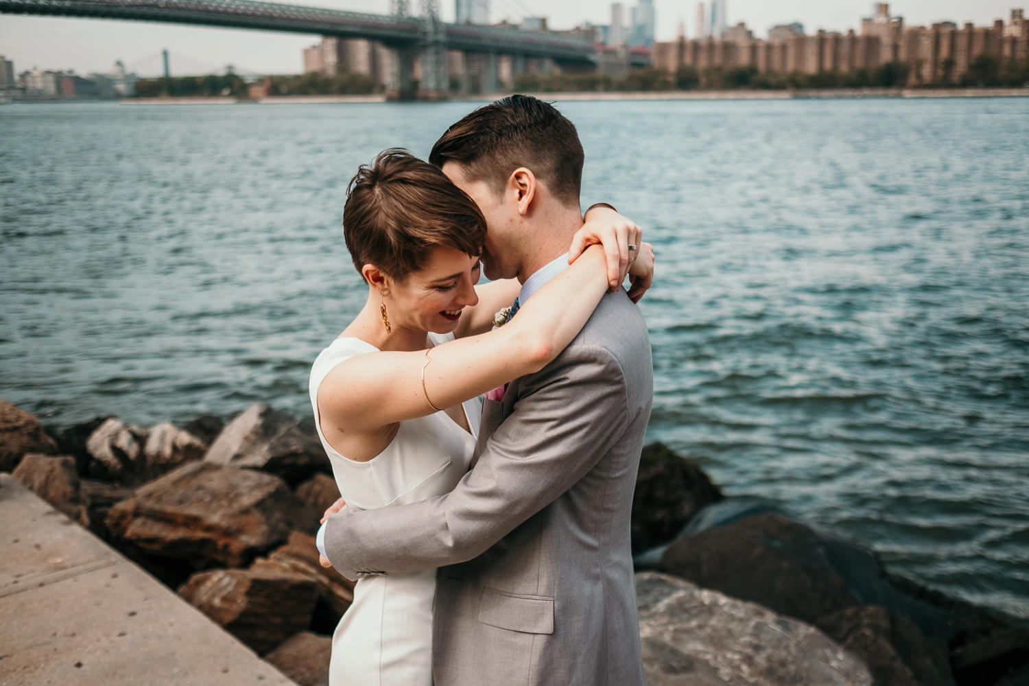 newlyweds hugging arms around waist and shoulders water in background