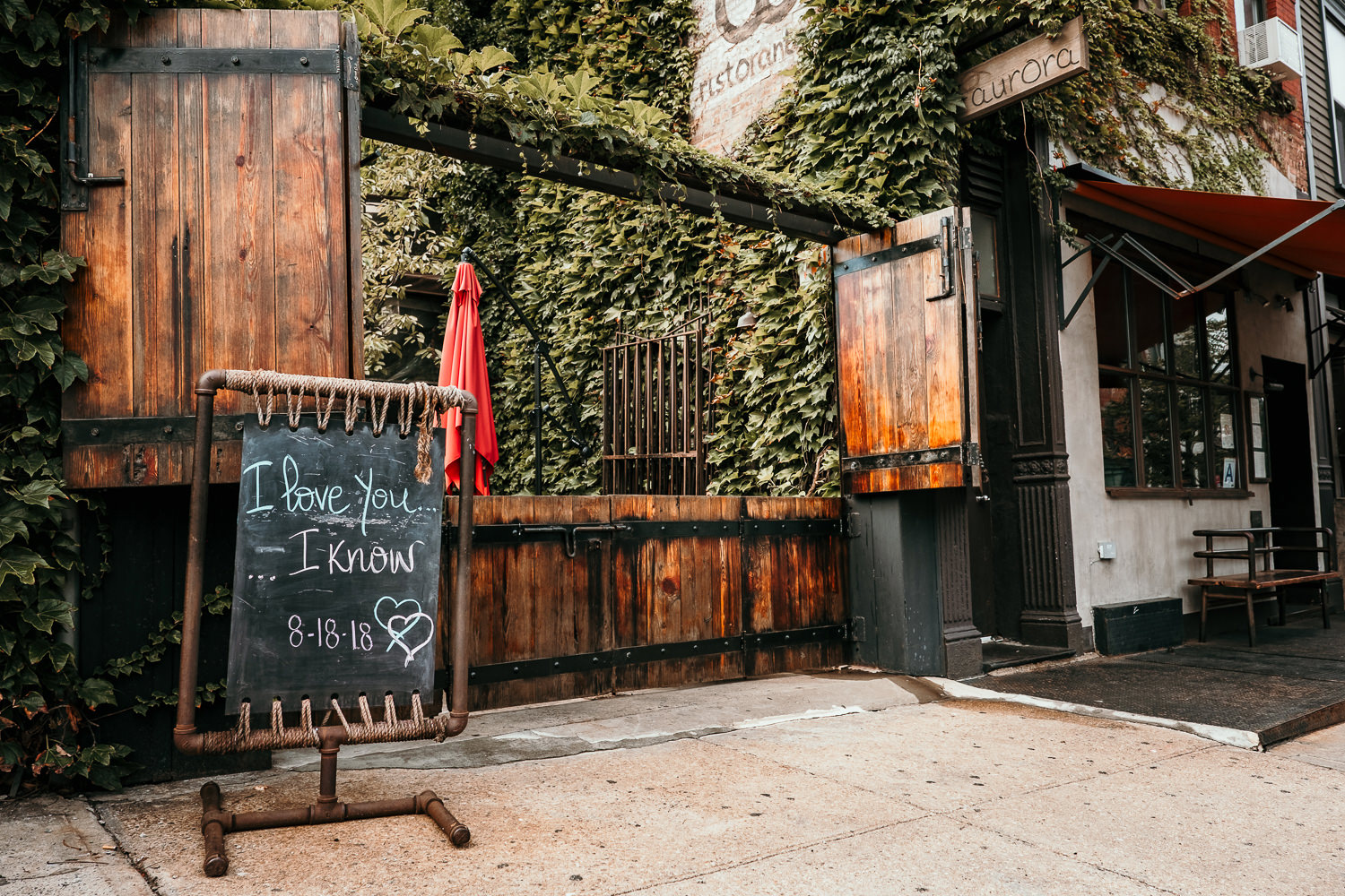 entrance to restaurant green walls wooden doors sign written in chalk says I love you I know