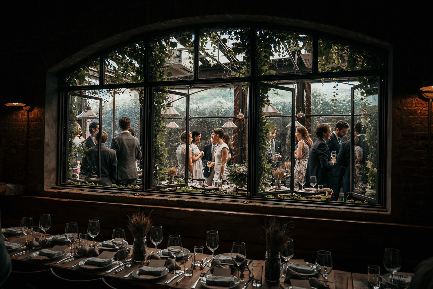 inside restaurant looking out at all the wedding guests thru windows covered in vines