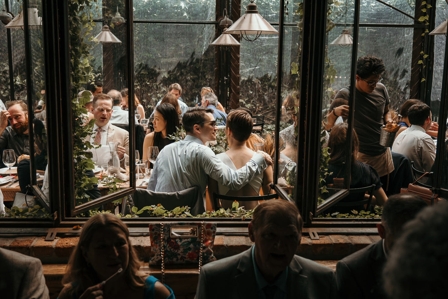 inside looking out thru vine covered windows newlyweds in middle looking at each other
