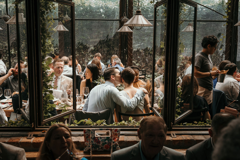 inside looking thru windows back of newlyweds sitting at their table groom kissing her cheek