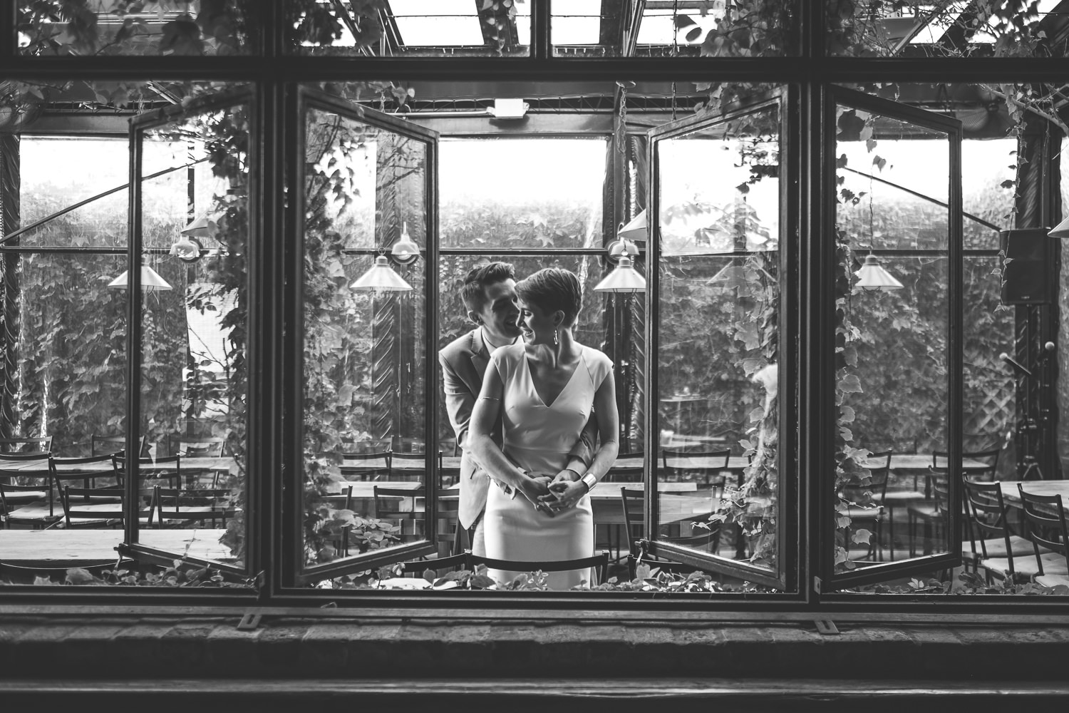inside looking outside vine covered windows newlyweds in middle window hugging