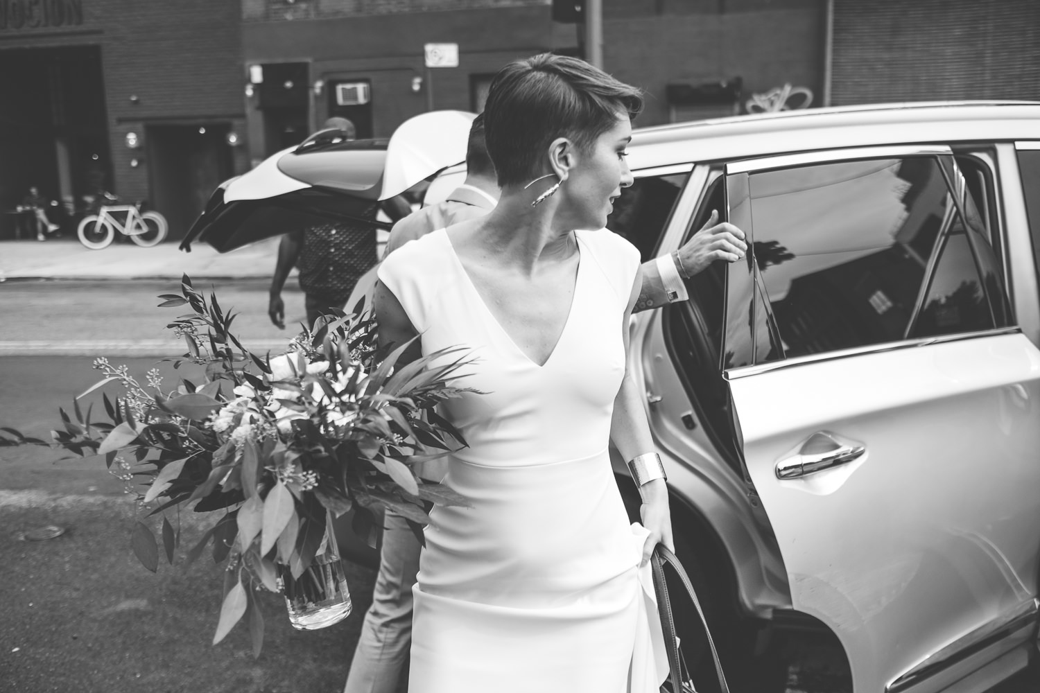 black and white bride holding flowers getting out of car Brooklyn street