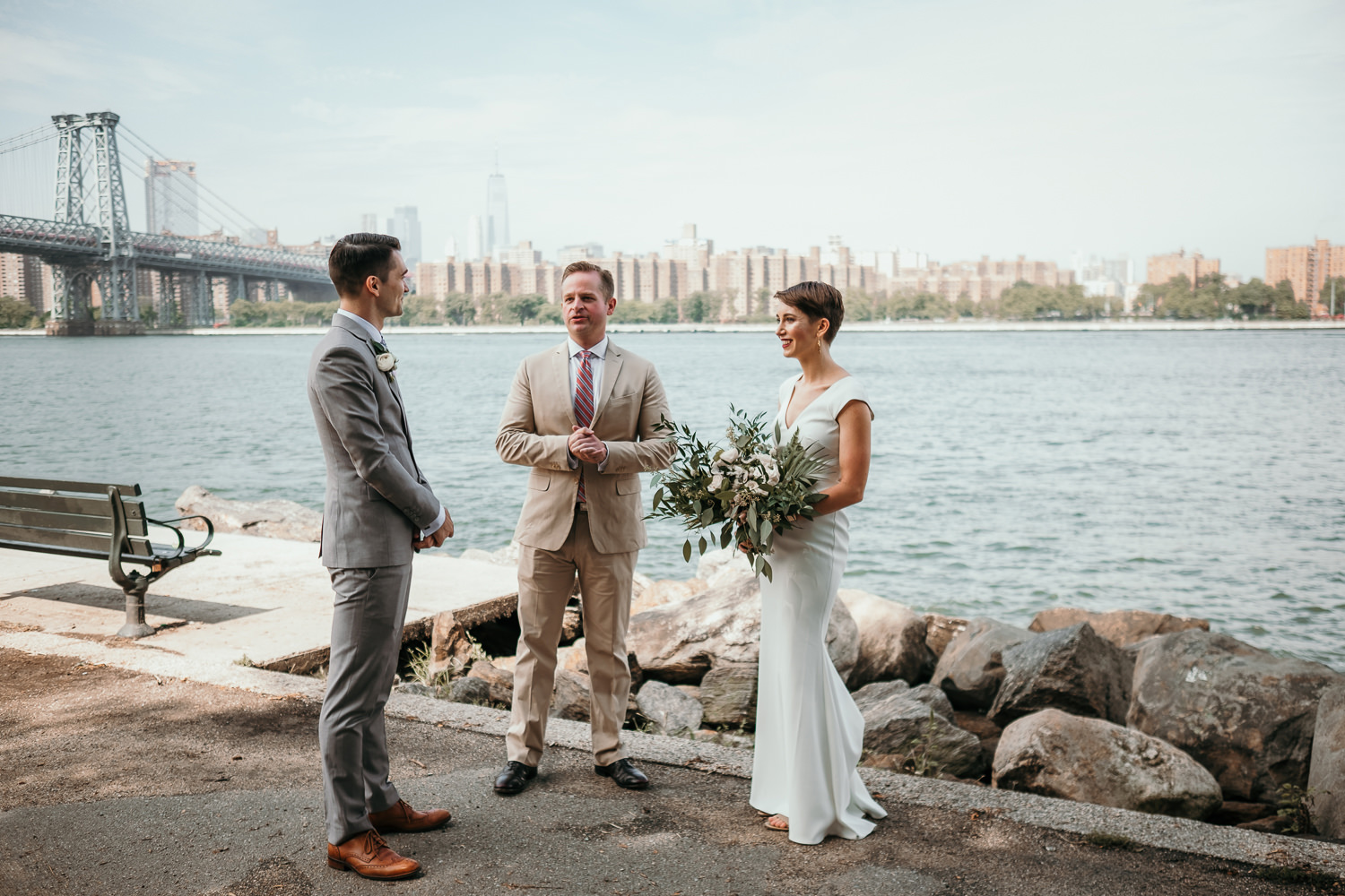 couple facing each other officiant in middle view of Brooklyn bridge