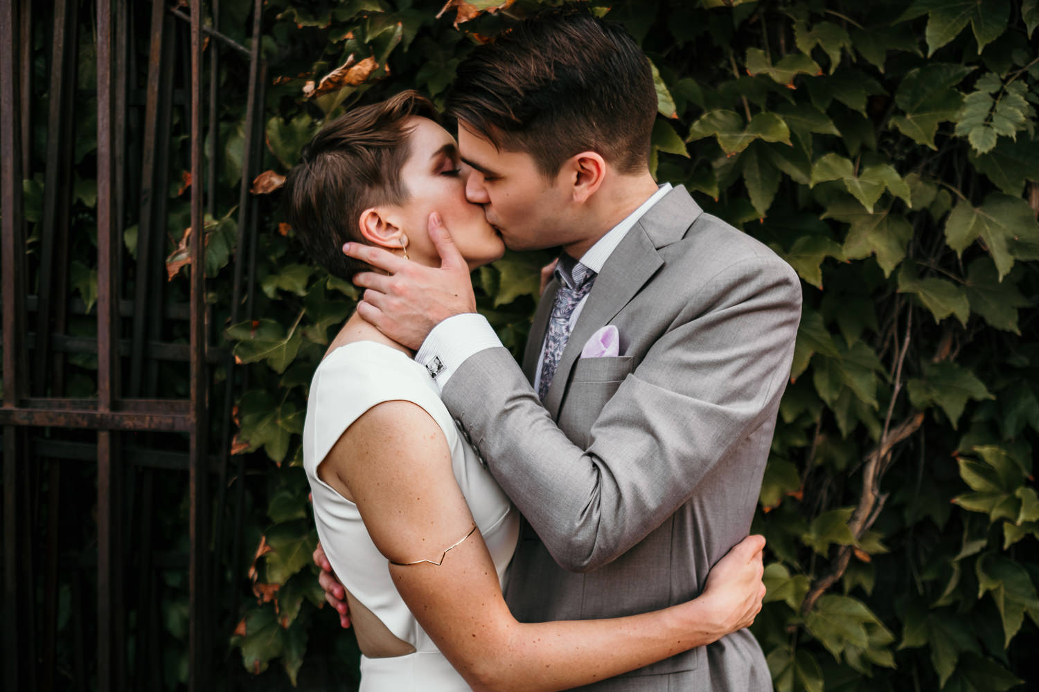 newlyweds hugging and kissing in front of green leaf covered wall