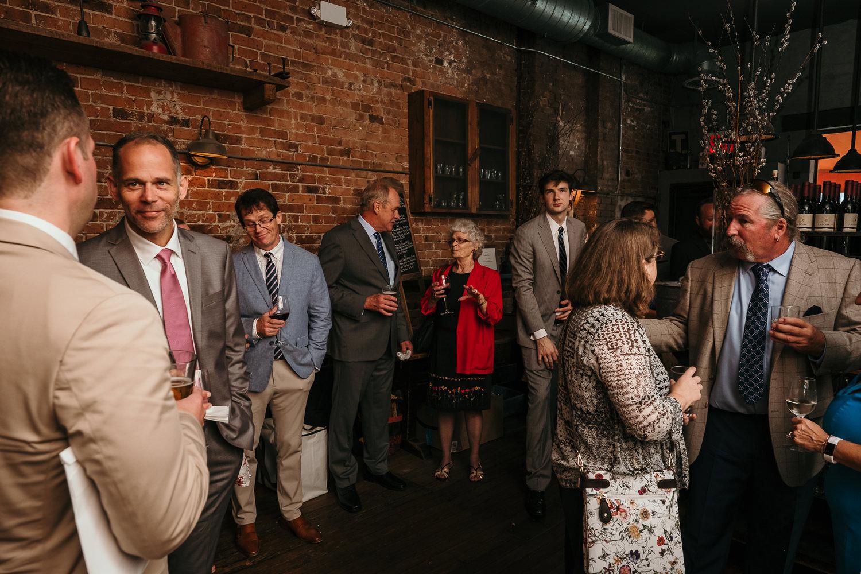 wedding guests inside aurora mingling holding drinks
