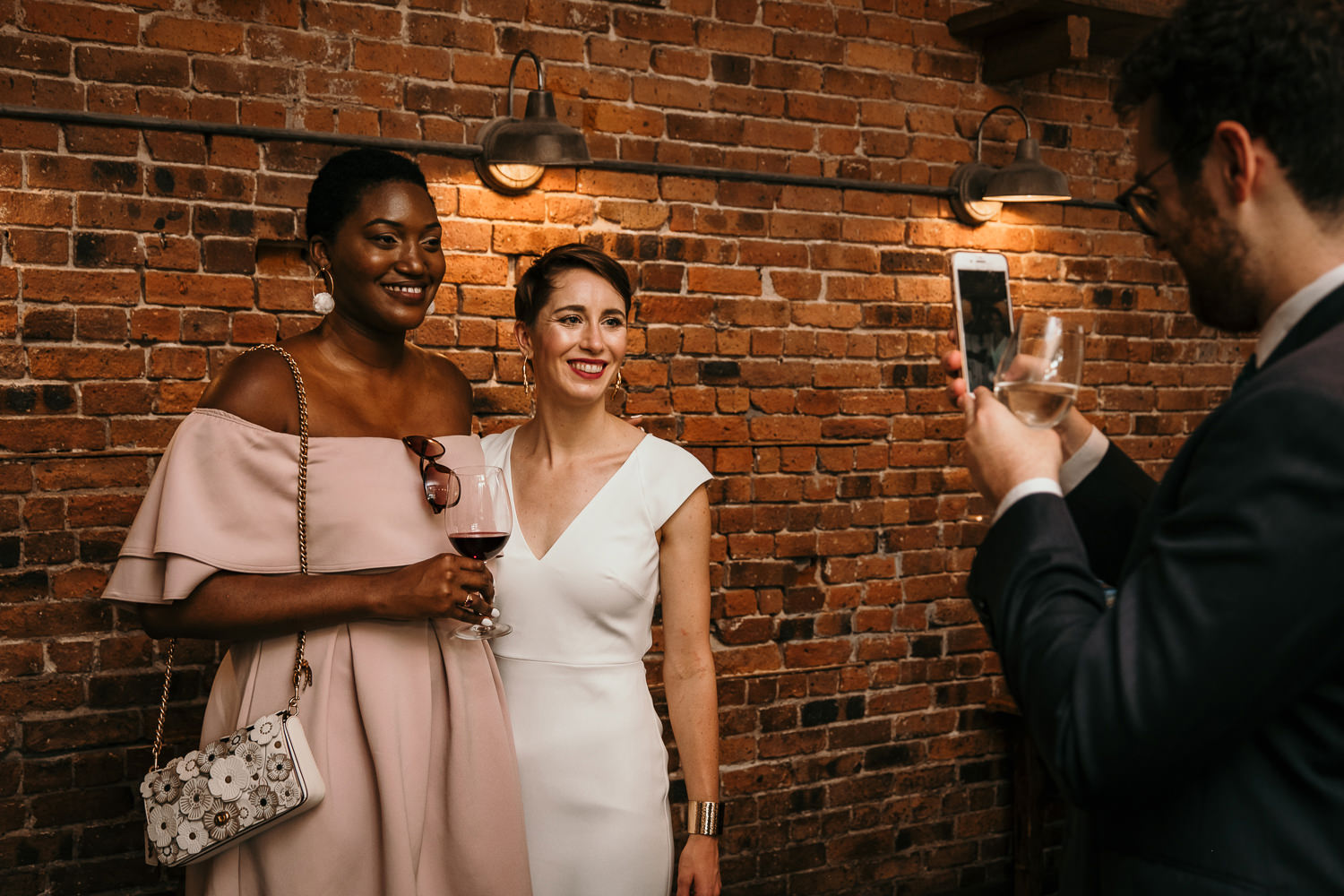 bride and friend posing in front of brick wall other friend taking a cell phone picture