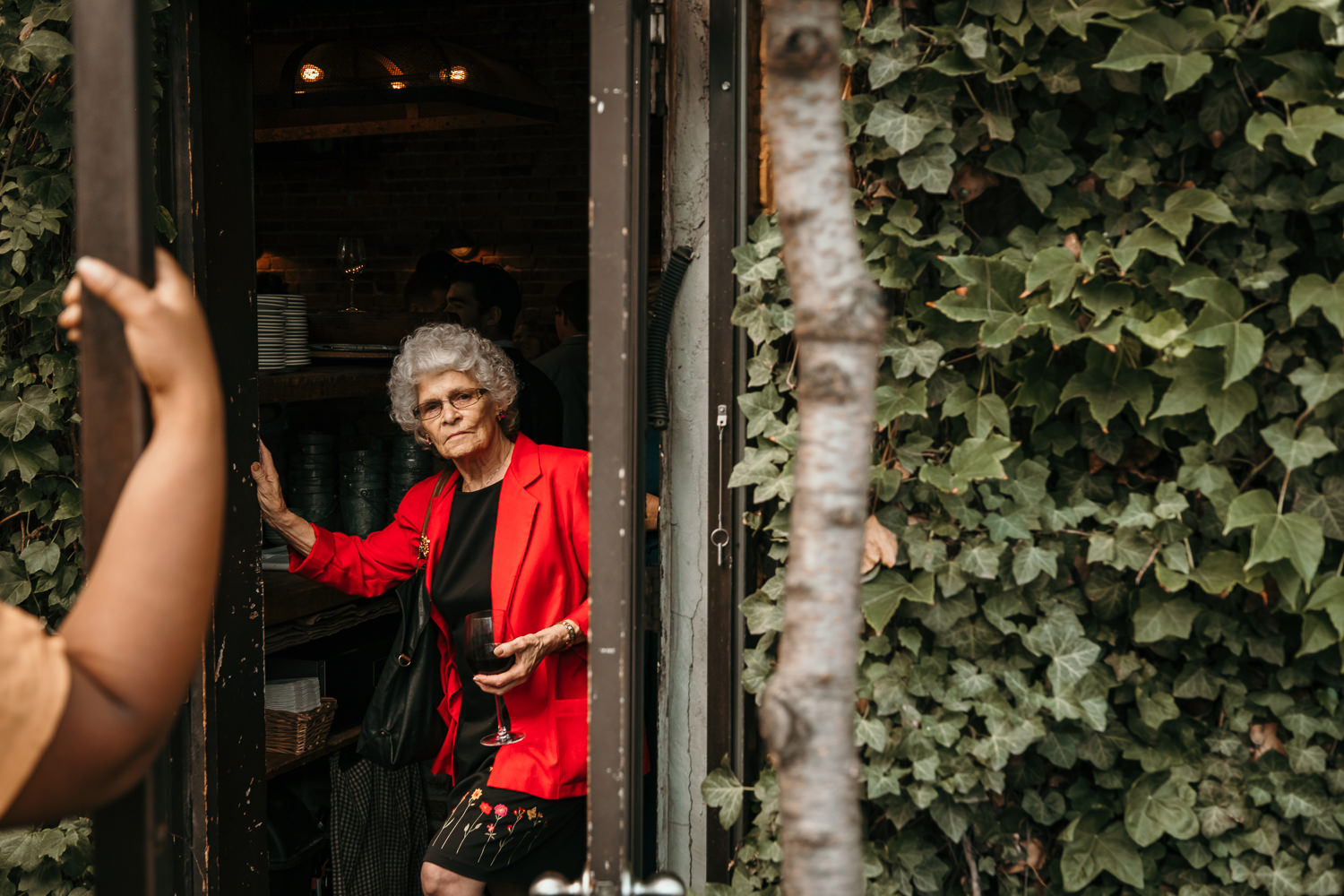 outside looking in, older lady wearing black dress and red blazer resting on the door