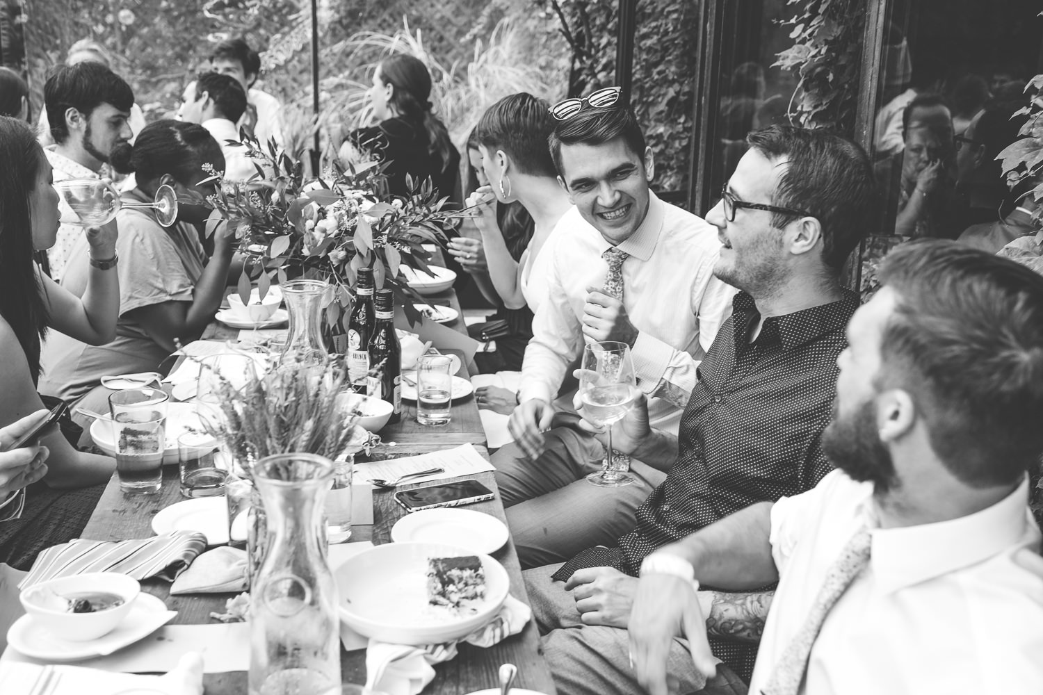 black and white close up of bridal table groom laughing with best man