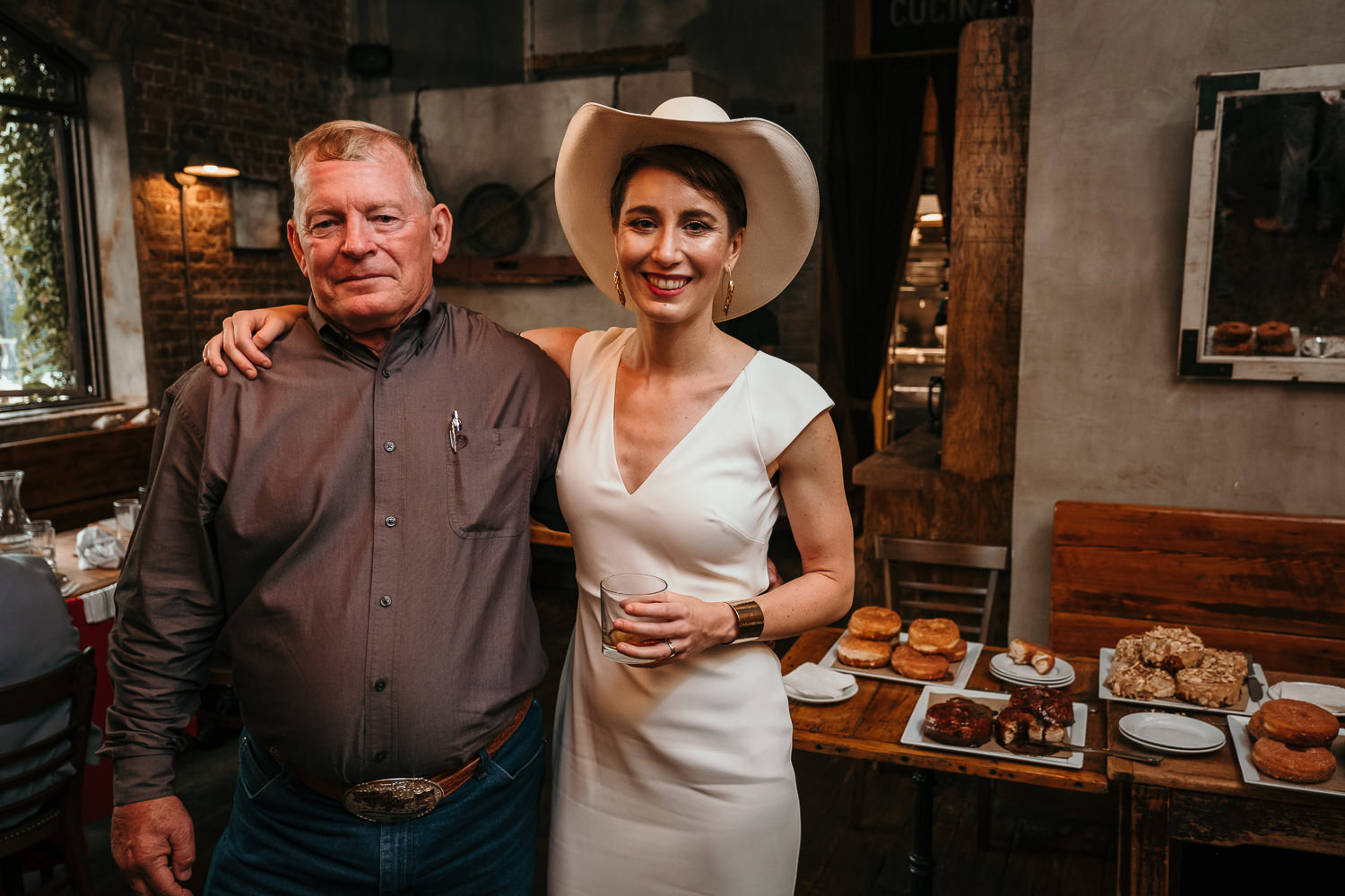 bride wearing cowboy hat posing with older male family member