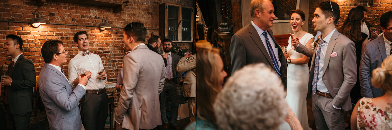 wedding guests inside aurora mingling laughing hard