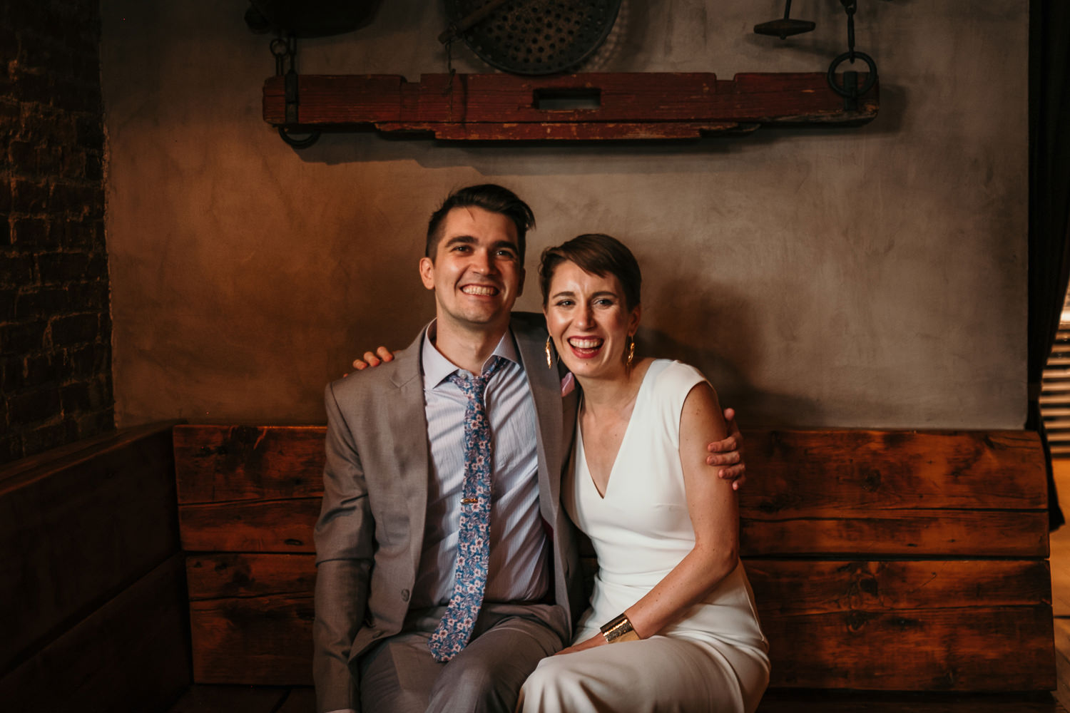 newlyweds sitting on wooden bench inside restaurant laughing at camera concrete wall