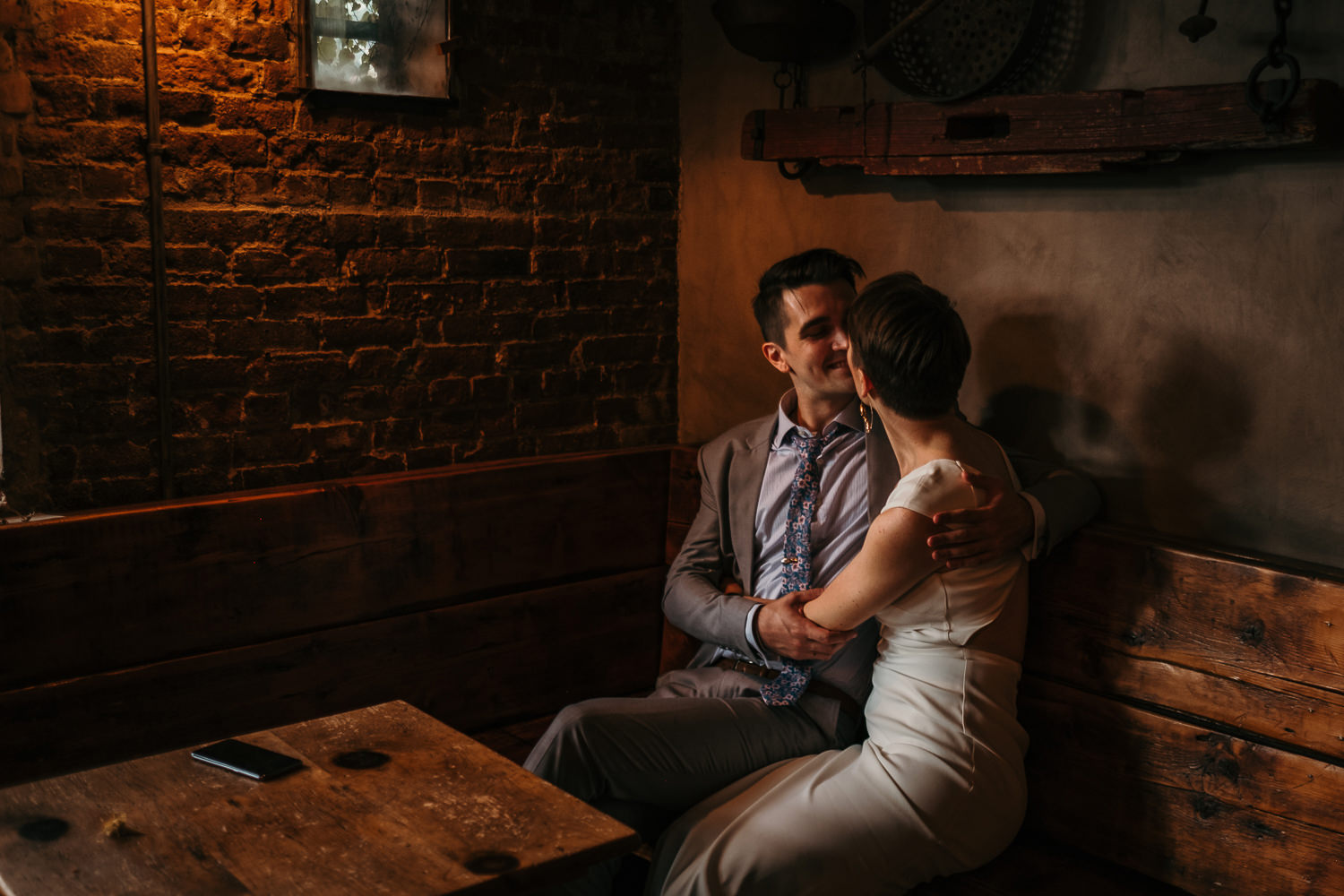 moody lighting room corner brick and concrete wall newlyweds sitting and hugging