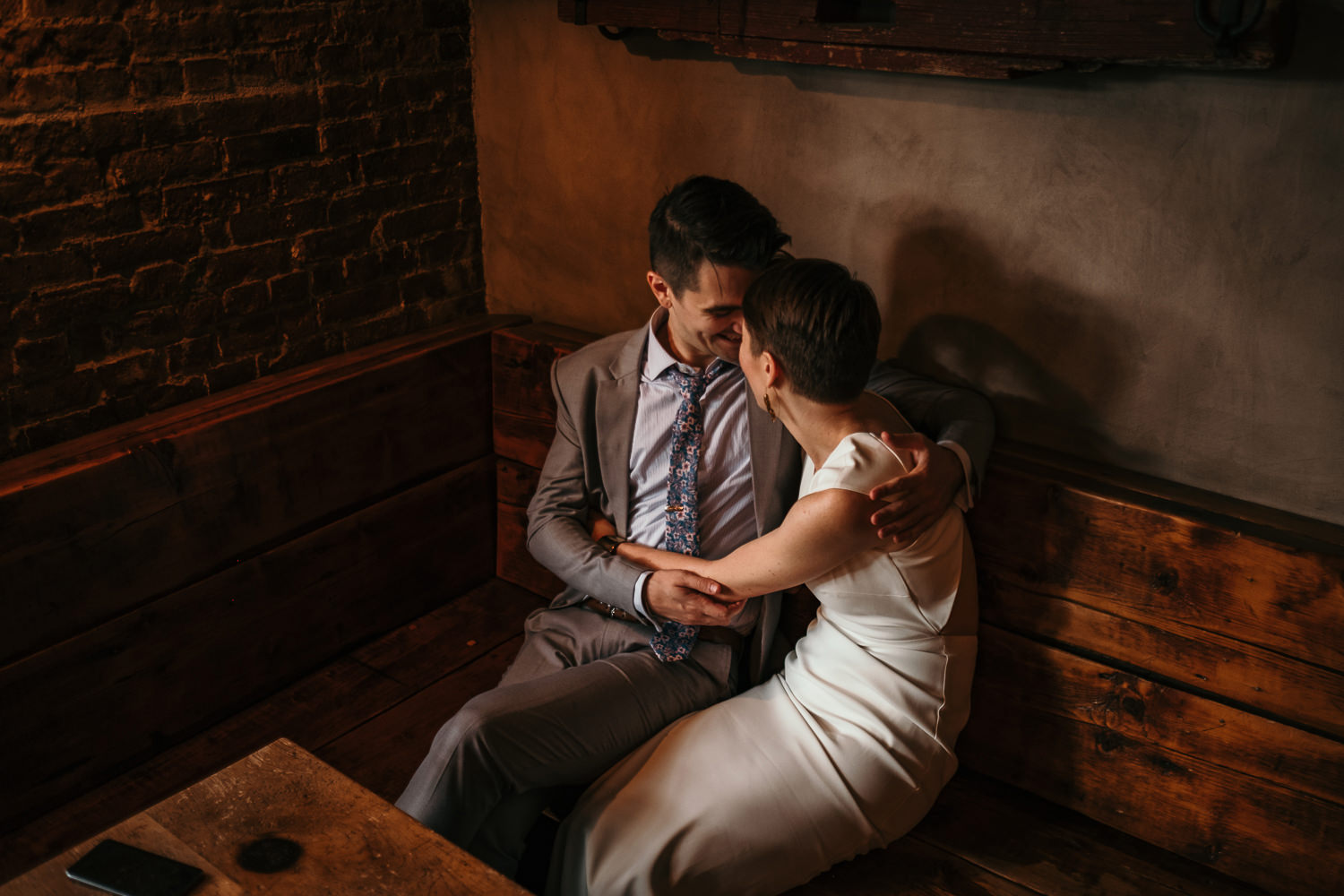 close up of newlyweds sitting on wooden bench hugging foreheads touching