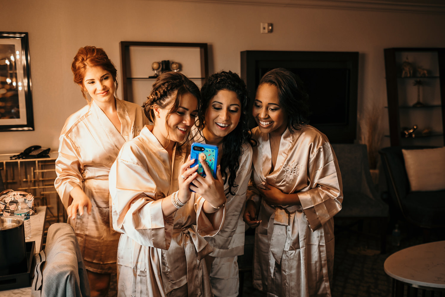 bridesmaids looking at selfies on phone