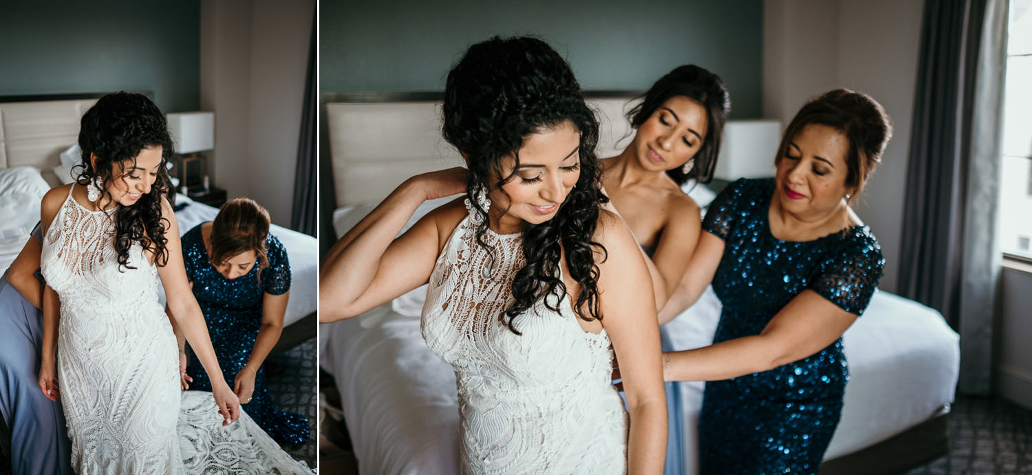mom and sister helping bride zip up dress
